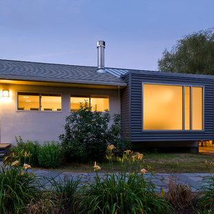 Imagen de fachada beige, actual, de una planta, con revestimiento de metal y tejado a dos aguas