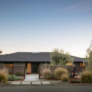 Esempio della facciata di una casa unifamiliare grande grigia contemporanea a un piano con rivestimento in stucco, tetto a padiglione e copertura a scandole