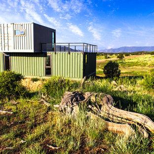 Foto de fachada verde, industrial, pequeña, de dos plantas, con revestimiento de metal y tejado plano
