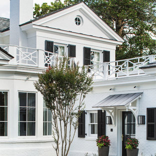 Inspiration for a mid-sized transitional white two-story brick exterior home remodel in New York with a tile roof