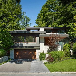 Foto på ett mellanstort funkis grått hus i flera nivåer, med blandad fasad