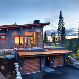 Example of a huge mountain style brown two-story stucco exterior home design in Denver