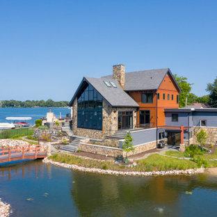 Réalisation d'une façade de maison orange chalet à un étage avec un revêtement en panneau de béton fibré, un toit à deux pans et un toit en shingle.