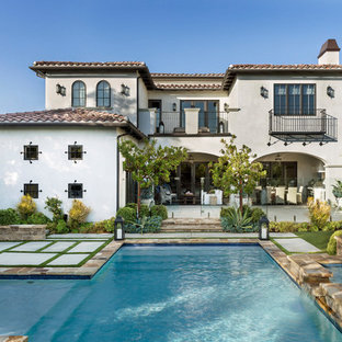 Photo of a mediterranean two-storey stucco white house exterior in Other with a hip roof and a tile roof.