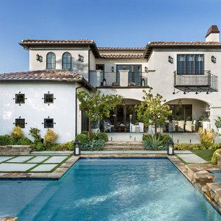 Imagen de fachada de casa blanca, mediterránea, de dos plantas, con revestimiento de estuco, tejado a cuatro aguas y tejado de teja de barro