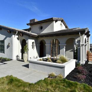 Ejemplo de fachada de casa beige, mediterránea, de tamaño medio, de dos plantas, con revestimiento de estuco, tejado plano y tejado de teja de barro