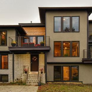 Foto på ett stort funkis beige hus i flera nivåer, med stuckatur och platt tak