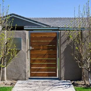 Mid-sized trendy beige two-story stucco house exterior photo in Los Angeles with a hip roof and a shingle roof