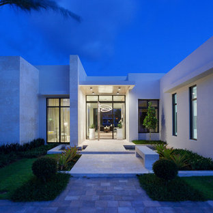 Mid-sized minimalist white one-story stucco flat roof photo in Miami