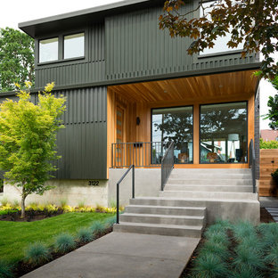 Large modern green two-story mixed siding flat roof idea in Portland