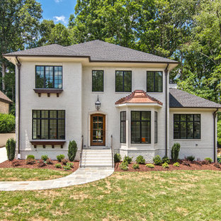 Large french country white two-story brick house exterior idea in Charlotte with a hip roof and a mixed material roof