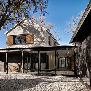 Example of a minimalist black two-story mixed siding house exterior design in Austin with a metal roof and a shed roof
