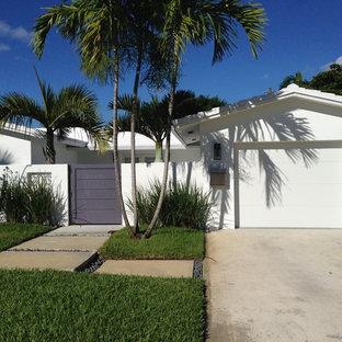 マイアミのトロピカルスタイルのおしゃれな家の外観 (白い屋根) の写真