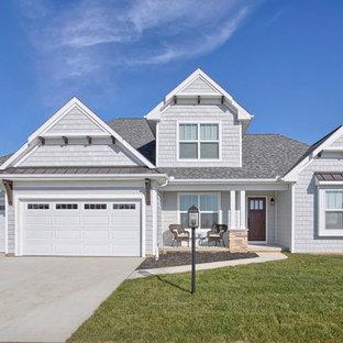 Cette photo montre une façade de maison grise chic de taille moyenne et à un étage avec un revêtement en vinyle et un toit à quatre pans.