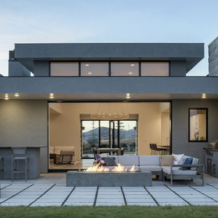 Large modern gray one-story stucco exterior home idea in Other with a metal roof