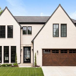На фото: большой, двухэтажный, бежевый частный загородный дом в викторианском стиле с облицовкой из цементной штукатурки, двускатной крышей и крышей из гибкой черепицы с
