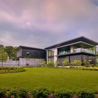Imagen de fachada de casa negra, moderna, grande, de dos plantas, con revestimientos combinados y tejado plano