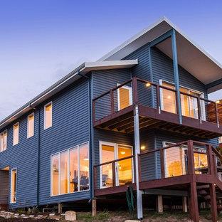 Ejemplo de fachada de casa pareada azul, rural, de tamaño medio, con revestimiento de aglomerado de cemento, tejado a la holandesa y tejado de metal