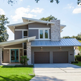 Mid-sized minimalist brown two-story stucco exterior home photo in Orlando with a shed roof