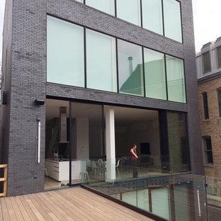 Diseño de fachada negra, moderna, grande, de tres plantas, con revestimiento de ladrillo