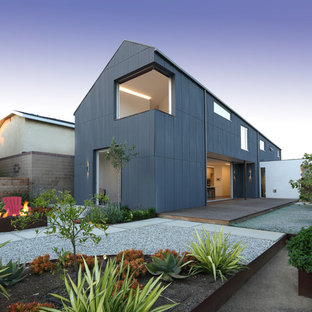 Large urban blue two-story metal house exterior photo in Los Angeles with a shingle roof
