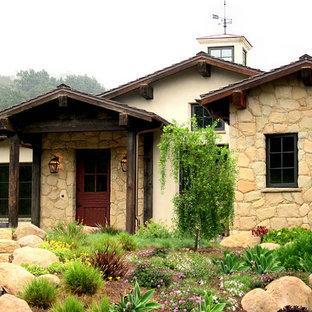 Imagen de fachada de casa beige, campestre, grande, de una planta, con revestimiento de piedra, tejado a dos aguas y tejado de teja de barro