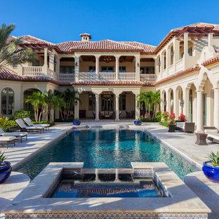 На фото: двухэтажный, бежевый дом в средиземноморском стиле с