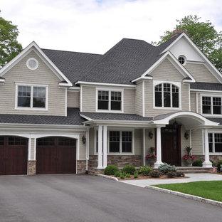 Ejemplo de fachada de casa gris, tradicional, grande, de dos plantas, con revestimiento de madera, tejado a cuatro aguas y tejado de teja de madera
