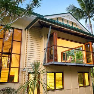 Foto de fachada de casa multicolor, tropical, grande, de dos plantas, con tejado a cuatro aguas y tejado de metal