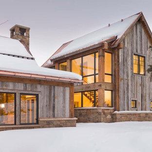 На фото: деревянный, большой, двухэтажный, зеленый частный загородный дом в стиле рустика с двускатной крышей