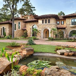 Idéer för ett mycket stort medelhavsstil beige hus i flera nivåer, med blandad fasad, valmat tak och tak med takplattor
