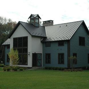 Imagen de fachada de casa azul, ecléctica, grande, de dos plantas, con tejado a dos aguas, tejado de metal y revestimiento de madera