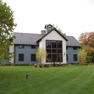 Ejemplo de fachada de casa azul, bohemia, grande, de dos plantas, con tejado a dos aguas, tejado de metal y revestimiento de madera