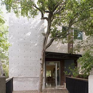Esempio della facciata di una casa grande grigia moderna a due piani con rivestimenti misti e tetto piano