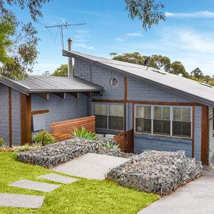Diseño de fachada gris, bohemia, grande, a niveles, con revestimiento de metal y tejado a doble faldón