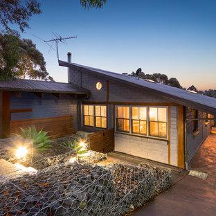 Modelo de fachada gris, ecléctica, grande, a niveles, con revestimiento de metal y tejado a doble faldón