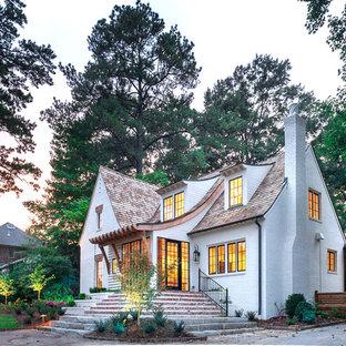 Foto på ett vintage vitt hus, med två våningar, tegel, sadeltak och tak i shingel
