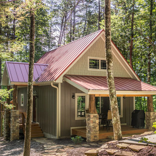 Example of a small mountain style brown two-story concrete fiberboard exterior home design in Other with a metal roof