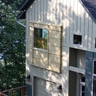 Diseño de fachada verde, ecléctica, grande, de dos plantas, con revestimiento de aglomerado de cemento y tejado a dos aguas
