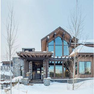 На фото: большой, деревянный, коричневый частный загородный дом в стиле рустика с разными уровнями, односкатной крышей и крышей из смешанных материалов