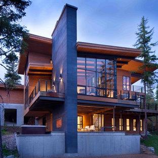 Immagine della facciata di una casa ampia marrone moderna a due piani con rivestimento in vetro
