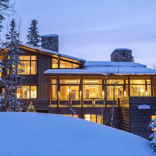 Ejemplo de fachada marrón, minimalista, extra grande, de tres plantas, con revestimientos combinados