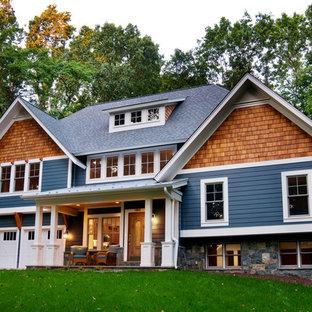 Ejemplo de fachada de estilo americano, de dos plantas, con revestimiento de madera