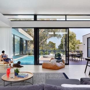 Imagen de fachada de casa gris, minimalista, grande, de una planta, con revestimiento de hormigón, tejado plano y techo verde