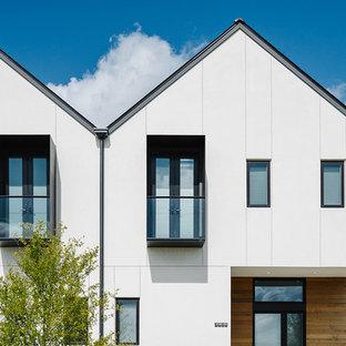 Пример оригинального дизайна: двухэтажный, белый дом среднего размера в скандинавском стиле с облицовкой из винила и двускатной крышей
