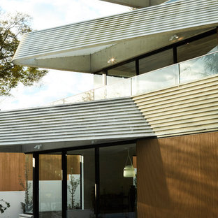 Modern grey house exterior in Sydney with three or more storeys, mixed siding and a flat roof.