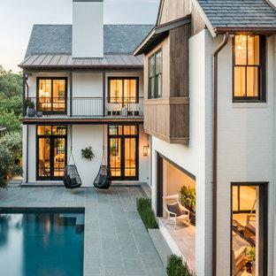 Imagen de fachada blanca, clásica renovada, de dos plantas, con revestimiento de ladrillo y tejado a dos aguas