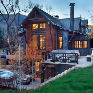Ejemplo de fachada marrón, rural, a niveles, con revestimientos combinados y tejado a dos aguas