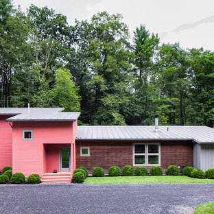 Trendy pink two-story mixed siding house exterior photo in New York with a shed roof and a metal roof
