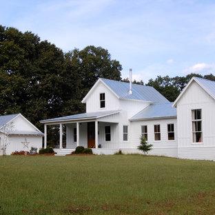 Immagine della facciata di una casa bianca country a due piani con rivestimento in legno